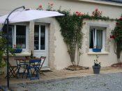 Terrasse du gîte, sa table et les rosiers